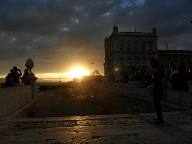 Pôr do sol visto da Praça do Comércio, no deque sobre o Rio Tejo