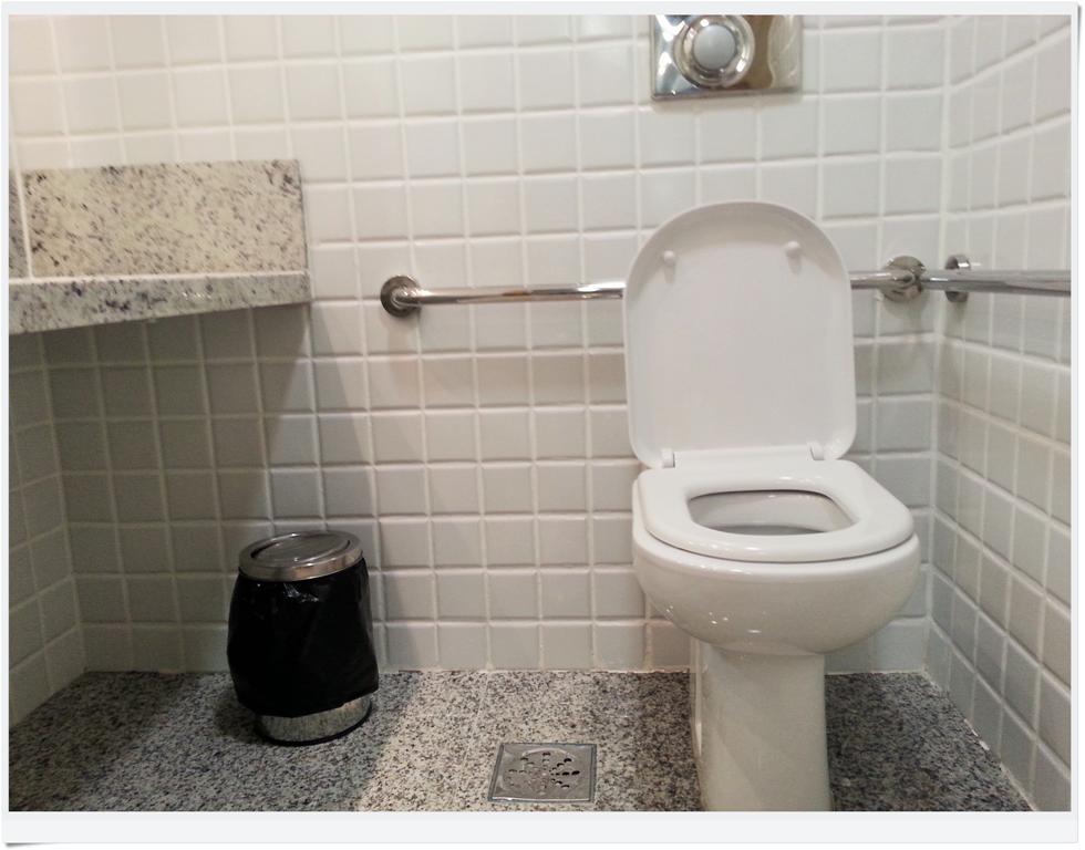 No banheiro, há barras de segurança, vaso sanitário sem a famigerada abertura frontal, espaço sob a pia para aproximação da cadeira de rodas. E a lixeira não tem pedal! Eba!
