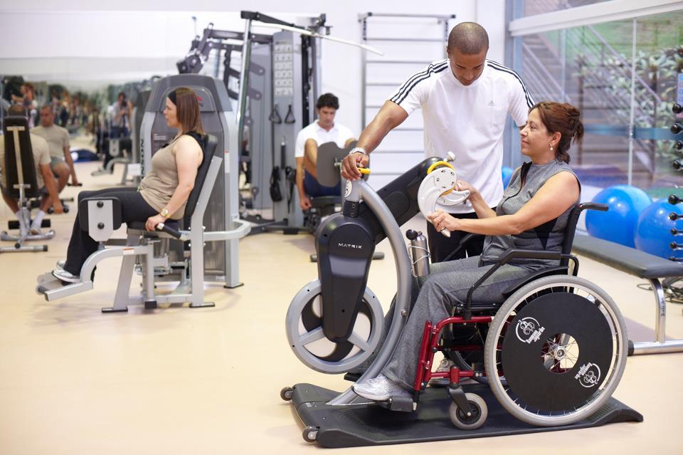 Esta foto é da divulgação do hotel, mostrando a cadeirante fazendo exercícios na bicicleta manual.