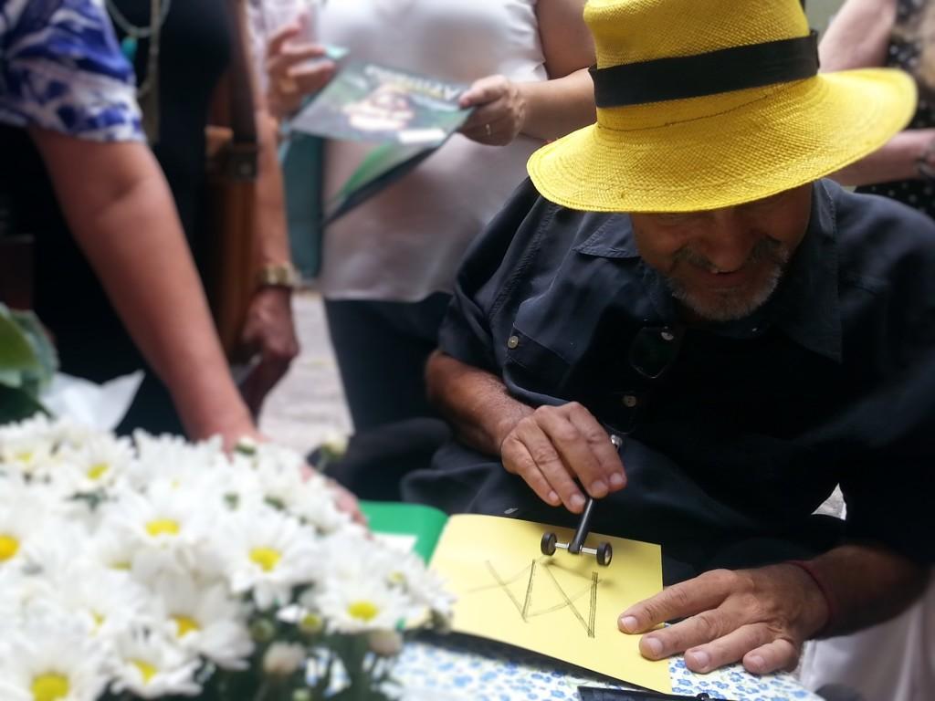 """Se a ELA limita os movimentos de Marcelo, não limita sua vida. Ele criou um jeito bem singular de """"autografar"""" os livros, usando um carimbo para registrar as iniciais de seu nome."""