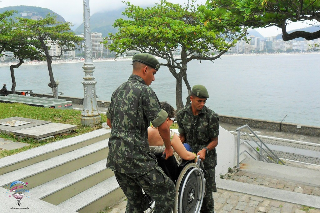 Sendo carregada pelos rapazes do Exército para conhecer a cúpula do Forte de Copacabana, que só era acessível por escadas. É claro que não te aconselho a fazer o mesmo. Tenho um bom equilíbrio de tronco e sou aventureira, por isso esse tipo de loucura... ;)