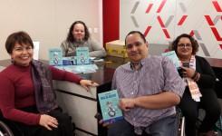 Jairo está à frente, mostrando seu livro. No seu lado esquerdo na foto, estamos eu e Carlos Jota Guedes. À direita dele, está a Mariane.