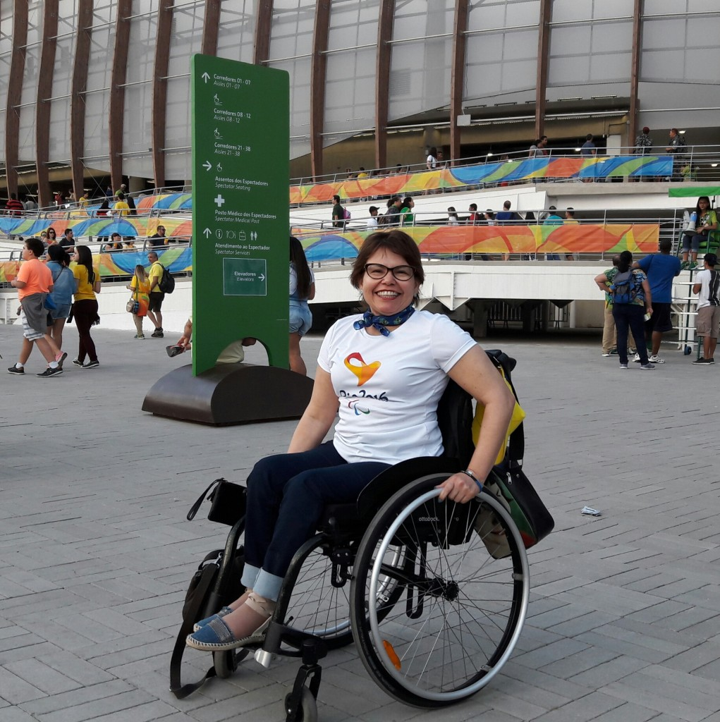Estou em frente à Arena Olímpica 3, para assistir ao jogo de bocha. Estou vestida com a camisa que contém a logo da Paralimpíada e com bandana com as cores da bandeira brasileira.