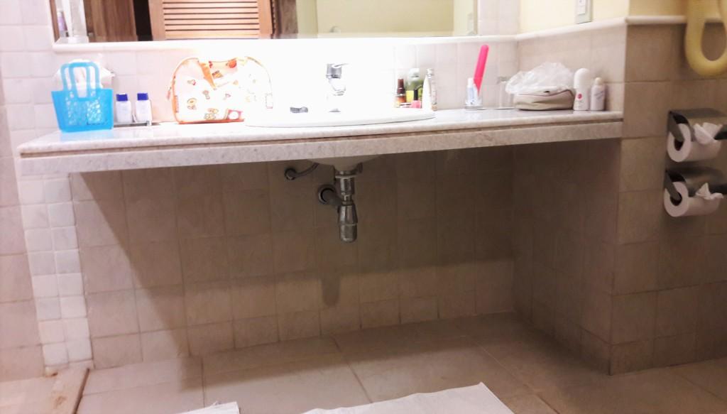 O banheiro é amplo, com área de giro. Pia sem fechamento permite aproximação frontal.