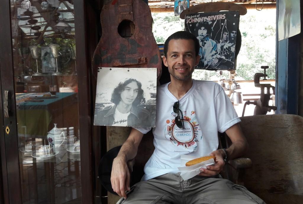 Leo posa para a foto ao lado de capa de disco de Flávio Venturini, no museu de quinquilharias/lanchonete Jeca Tatu.